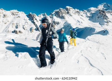 Sportsmen is walking on the mountain with snowboards and skies