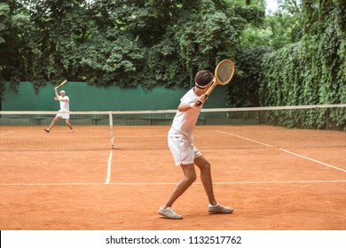 sportsmen in white sportswear playing tennis with wooden rackets on court