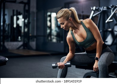 Sportsperson bending forward while having a seat and making a dumbbell biceps curl