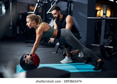 Sportsperson covering a medicine ball with her palms and raising her torso with a coach telling what to do