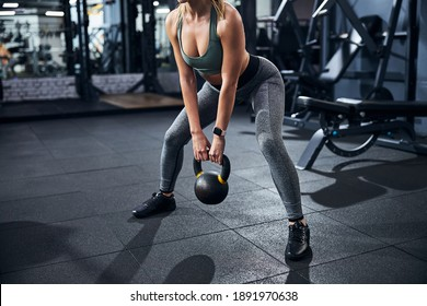 Sportsperson performing a kettlebell sumo squat with her feet fixed firmly on a wider than shoulder-width level