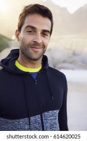 Sportswear guy smiling on beach, portrait