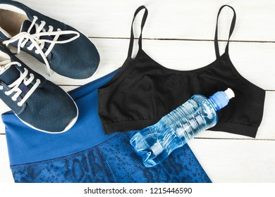 Sportswear and water bottle on wooden background. Concept sport.