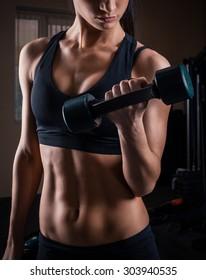 sportswoman do exercises with dumbbells