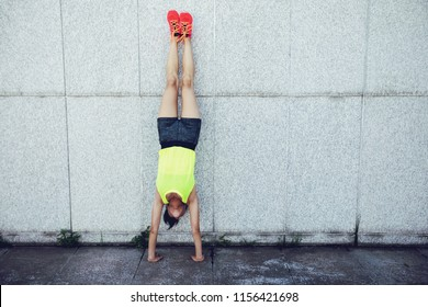 Sportswoman doing a handstand against a marble wall