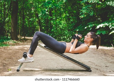 Sportswoman doing sit ups in nature. Exercise healthy lifestyle concept.