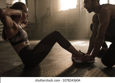 Sportswoman doing sit-ups while a fitness trainer holding her feet. Female doing abs exercise with help from a man in gym.