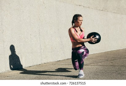 Sportswoman doing stretching exercise with medicine ball. Muscular woman exercising fitness ball outdoors.