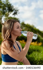 sportswoman drinks water from plastic bottle in the park after training