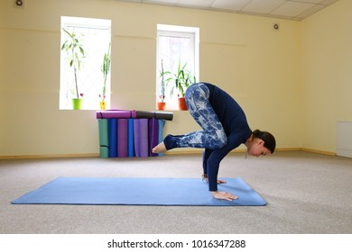 Sportswoman focused on stretch before Pilates class. Girl doing warm up for legs on mat. Female has hair pulled back, concentrated look. Athlete dressed in dark top, yoga legging trains in fitness