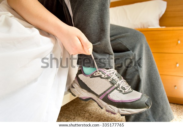 sportswoman gets up of the bed and tie shoelaces to be ready for jogging with tracksuit and running shoes