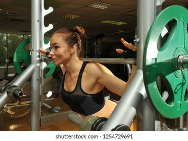 Sportswoman in the gym. Lifting barbell. Load. Energy. Trained body. Female figure on a dark background