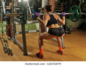 Sportswoman in the gym. Lifting barbell. Load. Energy. Trained body. Female figure on a dark background.