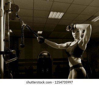 Sportswoman in the gym. Work on simulators. The load on the muscles. Energy. Trained body. Female figure on a dark background. Monochrome image. Sepia.
