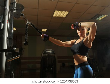 Sportswoman in the gym. Work on simulators. The load on the muscles. Energy. Trained body. Female figure on a dark background.