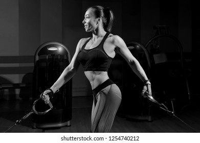 Sportswoman in the gym. Work on simulators. The load on the muscles. Energy. Trained body. Female figure on a dark background. Monochrome image.