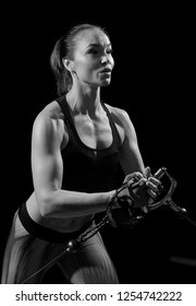 Sportswoman in the gym. Work on simulators. The load on the muscles. Energy. Trained body. Female figure on a dark background. Monochrome image