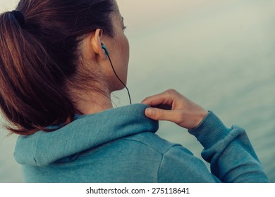Sportswoman in headphones workout on coast in summer in the morning