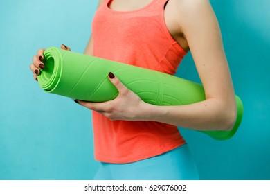 Sportswoman holding twisted fitness mat