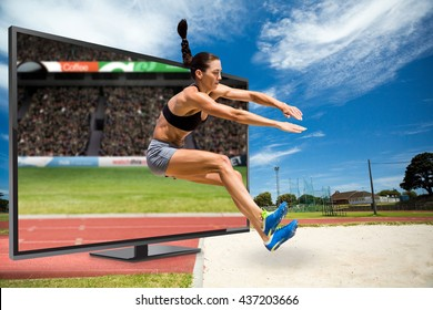 Sportswoman jumping on a white background against view of a stadium
