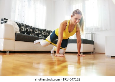 Sportswoman kneeling on the floor at home and stretching power rubber with legs. Exercises for thighs.