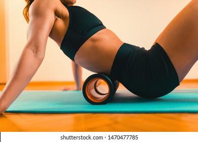 Sportswoman Massaging Lower Back with Foam Roller
