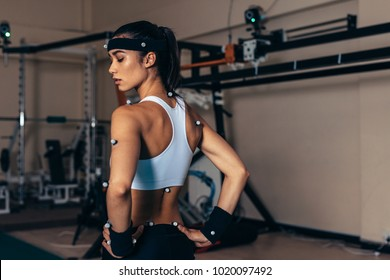 Sportswoman with motion capture sensors on her body to measure the movement during sports at biomechanical lab.