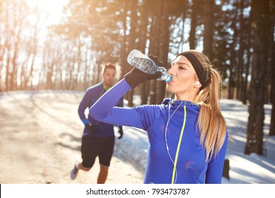 Sportswoman on condition training drinking water in snowy nature