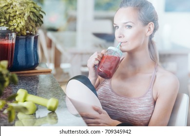 Sportswoman on detox diet purifying body by drinking healthy red cocktail after gymnastics