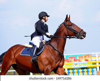 The sportswoman on a horse. The horsewoman on a red horse. Equestrianism. Horse riding. Horse racing. Rider on a horse.