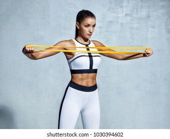 Sportswoman performs exercises for the muscles of the chest. Photo of young woman workout with resistance band on grey background. Strength and motivation.