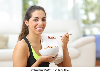 Sportswoman posing holding a bowl with cereals after sport at home