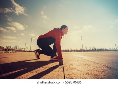 Sportswoman in ready position to run.Girl on the knee, preparing to start jogging.Achievements and goals.Looking to the future