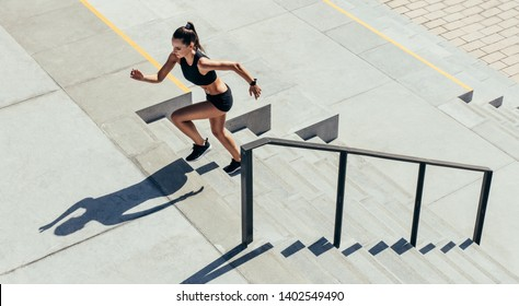 Sportswoman running up the steps as a part of workout routine. Female in sportswear exercising on staircase outdoors.
