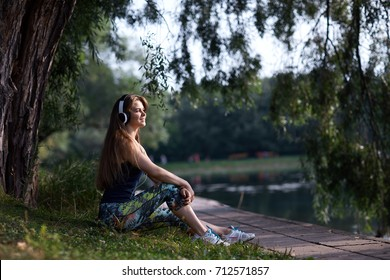 The sportswoman sits ashore in earphones and looks at sunrise.