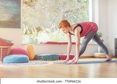 Sportswoman in sportswear stretching on a mat near the window, at home