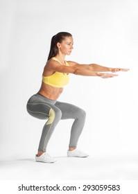 sportswoman squating isolated on white background