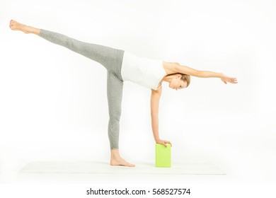 Sportswoman standing on yoga mat and doing Ardha Chandrasana posture, Half Moon Pose with yoga block isolated on white