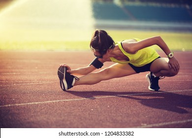 Sportswoman stretching before run on stadium