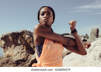 Sportswoman stretching her arm muscle at the beach, looking aside. Fit young african female doing warmup exercise outdoors.