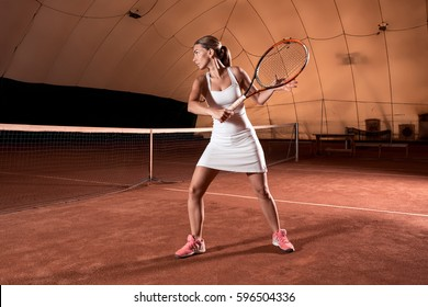 Sportswoman at the tennis court with racquet.