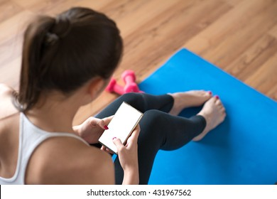 Sportswoman using a mobile phone in the gym.