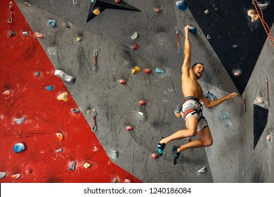 Sporty active businessman engaged in his hobby-bouldering. Equipped with belay system male athlete training in a colorful climbing gym, preparing to summer mountain ascend