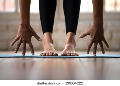 Sporty active woman practicing yoga, doing Standing forward bend exercise, head to knees uttanasana pose, wearing black sportswear pants, indoor close up, yoga studio or home. Well being concept