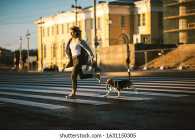 Sporty active woman running across pedestrian road with dog on leash in city in sunny day