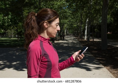sporty adult woman with red sweater, watching mobile smartphone in park of Retiro, in Madrid, Spain. Horizontal shot