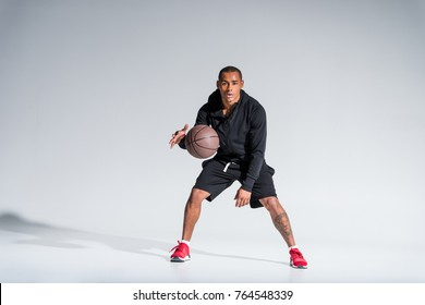 sporty african american man playing with basketball ball and looking at camera on grey