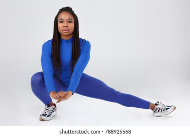 A sporty African-American girl, in a blue tight suit, makes deep squats and holds hands in front of her. Isolated.