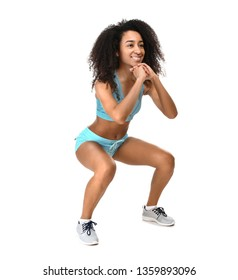 Sporty African-American woman doing squats on white background