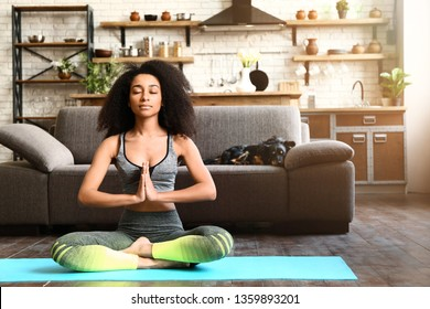Sporty African-American woman practicing yoga at home